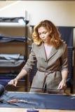 裁缝妇女与测量的磁带一起使用在工作室 库存照片