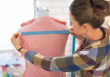 裁缝妇女与礼服一起使用在演播室 库存图片