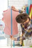 裁缝妇女与礼服一起使用在演播室 免版税库存照片