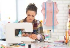 裁缝妇女与缝纫机一起使用 库存图片