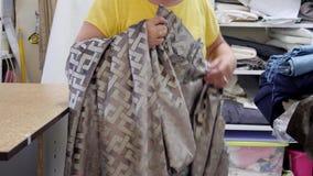 裁缝寻找缝合的帷幕的织品样品 影视素材