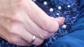 裁缝手特写镜头缝小珠的对与衣服饰物之小金属片的蓝色织品 股票视频