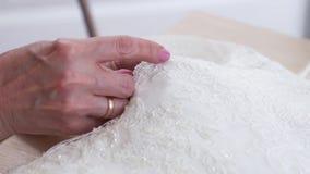裁缝手特写镜头缝小珠的对典雅的鞋带织品 影视素材
