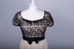 裁缝时装模特在一件米黄和黑鞋带礼服穿戴了 库存图片