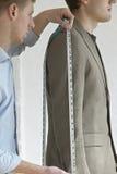 裁缝测量的顾客的衣服 免版税图库摄影