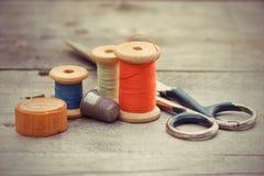 裁缝的工具-老剪刀,螺纹,磁带centim短管轴  免版税库存照片