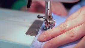 裁缝的手降低缝纫机的针 她开始缝合衣裳 股票视频