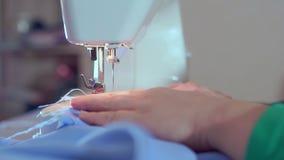 裁缝的手降低缝纫机的针 她开始缝合衣裳 影视素材