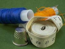 裁缝的米和多彩多姿的螺纹在绿色背景说谎 免版税库存照片