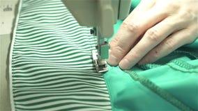 裁缝缝合在一台缝纫机的衣裳从蓝色织品 股票录像