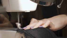 裁缝缝合衣裳由红色布料制成在一台缝纫机 工作在固定硬件灯的光旁边 股票录像