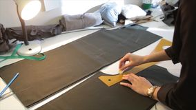 裁缝 手山谷裁缝裁缝` s剪布料 女性在工作场所的裁缝缝的材料 织品为做准备 免版税库存照片
