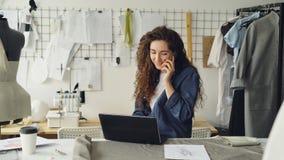 裁缝` s商店成功的店主在手机谈话并且使用膝上型计算机 批评衣物,缝纫机射击和 股票视频