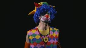 破裂入邪恶的笑的年轻英俊的小丑 股票录像