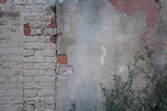 破裂和过时涂灰泥的砖墙 免版税库存照片