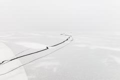 崩裂在用雪盖的一个冻湖的冰 免版税库存照片