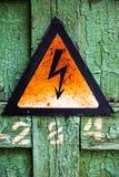 破裂的木表面上的老生锈的警告高压标志 库存照片