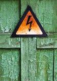 破裂的木表面上的老生锈的警告高压标志 免版税库存图片