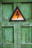 破裂的木表面上的老生锈的警告高压标志 库存图片