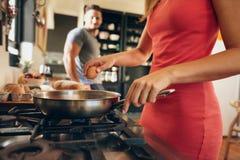崩裂鸡蛋的妇女入煎锅 免版税库存图片