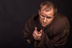 装扮一个叫化子的演员黑暗的背景的 库存照片