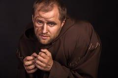 装扮一个叫化子的演员黑暗的背景的 免版税图库摄影