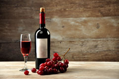 装瓶和一块玻璃用在一木cov的背景的红葡萄酒 库存照片
