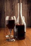 装瓶和一杯在一木backgroung的酒 库存图片