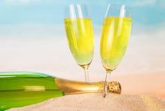 装瓶和两块玻璃用在沙子的香槟反对ba 免版税库存图片