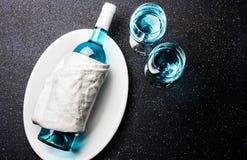 装瓶和两杯时髦蓝色酒 在黑背景的西班牙蓝色酒夏得乃白酒 花梢酒,顶视图 免版税库存图片