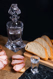 装瓶和小玻璃用与切片的伏特加酒在b的熏制的肉 库存图片