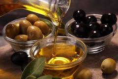 装瓶处女橄榄油和油在一个碗用一些橄榄 库存照片