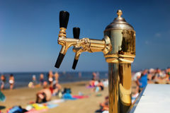 装瓶的啤酒的金黄起重机在夏天海滩 库存照片