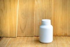 装瓶药物被做对塑料在木背景 使用包裹的墙纸或产品、药物图象和拷贝空间 免版税库存图片