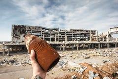 装着炸药的120 mm壳在手中与机场废墟 库存图片