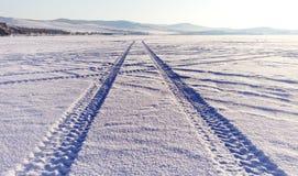 装胎在雪的轨道贝加尔湖冰表面上 免版税库存图片