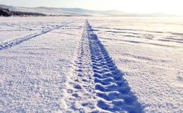 装胎在雪的轨道贝加尔湖冰表面上 免版税库存照片