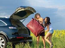装载一个大量袋子的妇女到汽车 免版税库存照片