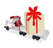 装载一个巨型礼物盒的牵引车拖车平板车 免版税库存图片