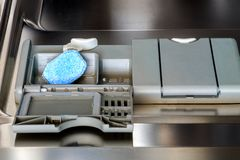 装载一种洗碗盘行为片剂入洗碗机 免版税库存图片