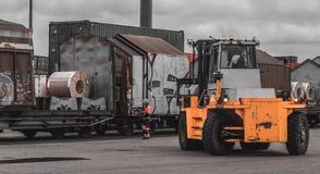 装载和卸载钢卷的过程在货物口岸 运载钢卷 起重器从无盖货车的作为卷 Stevedor检查 库存照片