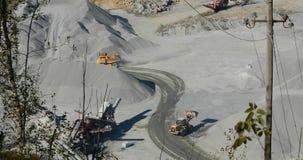 装载石头的巨大的黄色推土机提取入卡车,黄色推土机在翻斗车背后装载花岗岩 股票录像