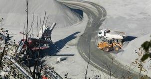 装载石头的巨大的黄色推土机提取入卡车,黄色推土机在翻斗车背后装载花岗岩 股票视频