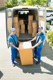 装载箱子的两名搬家工人在卡车 免版税库存照片