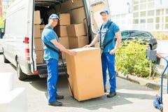 装载箱子的两名搬家工人在卡车 免版税库存图片