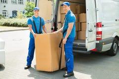 装载箱子的两名搬家工人在卡车 库存图片
