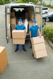 装载纸板箱的两名工作者在卡车 免版税库存照片