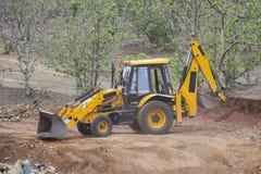 装载者在修路站点的反向铲挖掘者 免版税库存图片