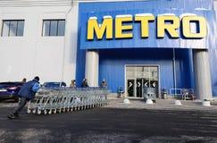 装载者在地铁大型超级市场附近推挤台车长的行  免版税库存图片