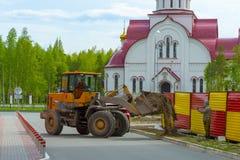 装载者拖拉机在城市卸载在一个花圃的地面土壤 库存照片